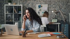 Mulher de sorriso que fala no telefone celular no escritório que trabalha com o portátil na mesa vídeos de arquivo