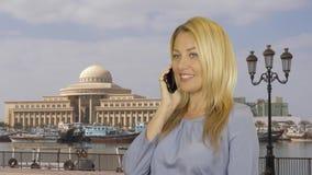 Mulher de sorriso que fala pelo telefone celular no navio do fundo que está no parque de estacionamento vídeos de arquivo