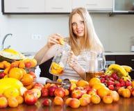 Mulher de sorriso que faz bebidas dos frutos Imagem de Stock Royalty Free