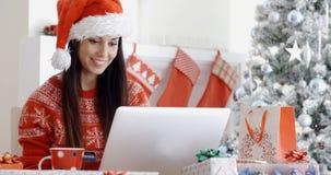 Mulher de sorriso que faz a compra em linha do Natal Fotografia de Stock