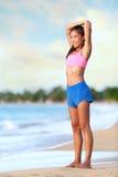 Mulher de sorriso que faz esticando o exercício na praia Fotografia de Stock Royalty Free
