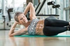 Mulher de sorriso que faz Excerise abdominal Imagem de Stock