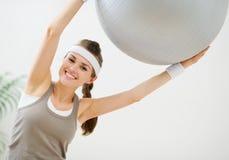 Mulher de sorriso que faz exercícios com esfera da aptidão Imagem de Stock