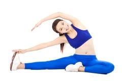 A mulher de sorriso que faz o exercício do núcleo, aquece o corpo Foto de Stock