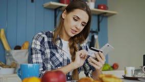 Mulher de sorriso que fazem a compra em linha usando o smartphone e cartão de crédito quando tenha o café da manhã na cozinha em  fotografia de stock
