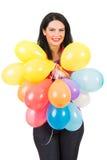 Mulher de sorriso que guarda balões da abundância Foto de Stock Royalty Free
