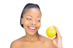 Mulher de sorriso que guarda e que olha a laranja Fotografia de Stock