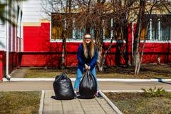 Mulher de sorriso que guarda grandes sacos de plástico com lixo foto de stock