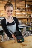 Mulher de sorriso que guarda o leitor de cartão do crédito Foto de Stock