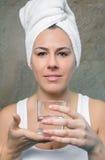 Mulher de sorriso que guarda o vidro da água em suas mãos imagem de stock