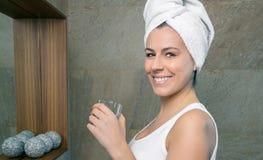 Mulher de sorriso que guarda o vidro da água no banho imagem de stock
