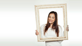 Mulher de sorriso que guardara uma moldura para retrato velha Imagens de Stock Royalty Free