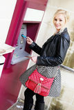 Mulher de sorriso que introduz um cartão em um ATM fotos de stock