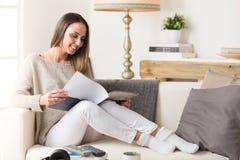 Mulher de sorriso que lê um compartimento em um sofá fotografia de stock royalty free