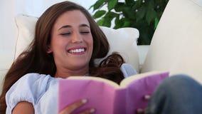 Mulher de sorriso que lê uma novela video estoque