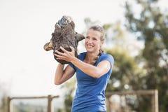 Mulher de sorriso que leva logs de madeira pesados durante o curso de obstáculo fotos de stock royalty free