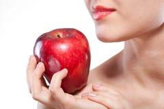 Mulher de sorriso que mantem a maçã vermelha isolada no branco Fotografia de Stock Royalty Free