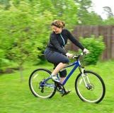 Mulher de sorriso que monta a bicicleta foto de stock