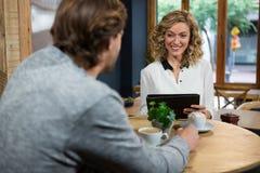 Mulher de sorriso que olha o homem na tabela na cafetaria fotografia de stock royalty free