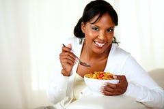 Mulher de sorriso que olha o que come o pequeno almoço Fotos de Stock