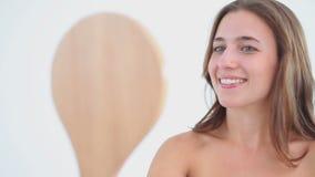 Mulher de sorriso que olha um espelho de mão filme