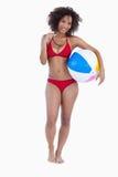Mulher de sorriso que prende uma esfera e óculos de sol de praia Fotografia de Stock