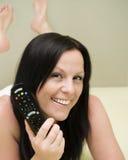 Mulher de sorriso que presta atenção à tevê na cama Fotografia de Stock Royalty Free