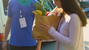 Mulher de sorriso que recebe o saco de mantimento do trabalhador da entrega, serviço do supermercado vídeos de arquivo