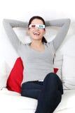 Mulher de sorriso que senta-se em um sofá com vidros 3D. Foto de Stock