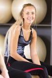 Mulher de sorriso que senta-se na bola do bosu no gym da aptidão Fotografia de Stock