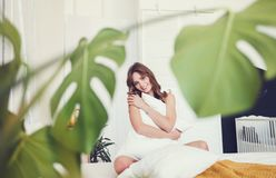 Mulher de sorriso que senta-se na cama foto de stock