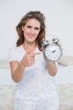Mulher de sorriso que senta-se na cama que aponta no despertador Imagem de Stock Royalty Free