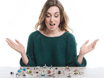 Mulher de sorriso que senta-se na frente dos anéis que encontram-se em uma tabela Fotografia de Stock