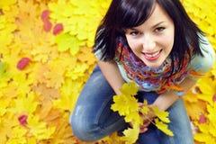 Mulher de sorriso que senta-se nas folhas caídas coloridas Foto de Stock Royalty Free
