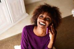 Mulher de sorriso que senta-se no assoalho e que fala no telefone celular Fotos de Stock