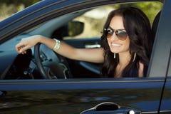 Mulher de sorriso que senta-se no carro, menina feliz que conduz o automóvel, para fora Fotografia de Stock Royalty Free