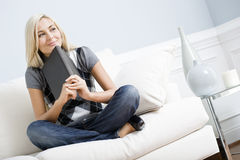 Mulher de sorriso que senta-se no sofá e em prender um livro imagem de stock royalty free