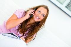 Mulher de sorriso que senta-se no sofá e que fala no telefone Imagens de Stock Royalty Free