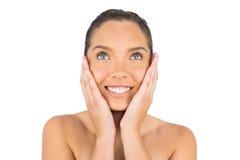 Mulher de sorriso que toca em sua cara e que olha para cima Imagem de Stock Royalty Free
