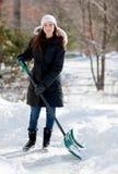 Mulher de sorriso que trabalha com pá a neve Foto de Stock