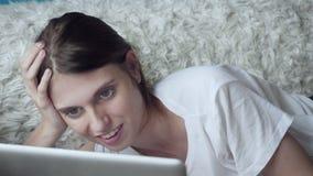Mulher de sorriso que usa o portátil em casa ao encontrar-se no sofá filme