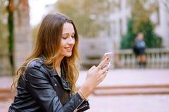 Mulher de sorriso que usa o smartphone na rua fotos de stock