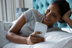 Mulher de sorriso que usa o telefone ao relaxar na cama fotografia de stock