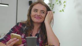 Mulher de sorriso que usa o telefone celular e bebendo o café dentro video estoque