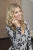 Mulher de sorriso que usa o telefone celular no escritório foto de stock