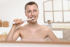 Mulher de sorriso que usa uma escova de dentes elétrica imagens de stock