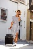 Mulher de sorriso que viaja com saco e telefone celular Imagem de Stock