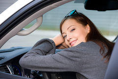 A mulher de sorriso senta-se no carro novo Fotos de Stock Royalty Free
