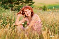 A mulher de sorriso senta-se no prado Imagem de Stock Royalty Free