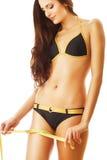 Mulher de sorriso 'sexy' no roupa de banho com medida no pé Foto de Stock Royalty Free